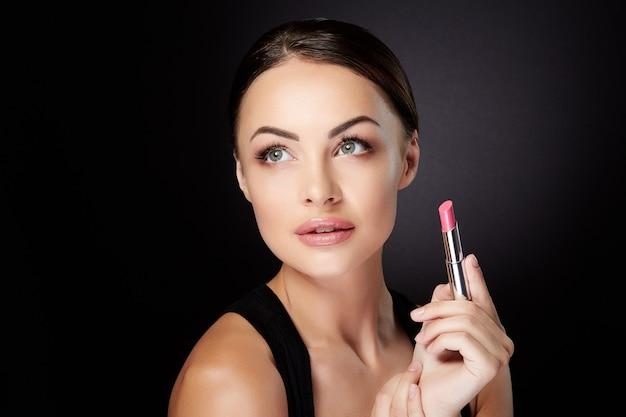 Conceito de beleza, cabeça e ombros de mulher jovem, olhando para cima e segurando o batom rosa. retrato da beleza da modelo com lábios rosados pintado com brilho labial, estúdio com fundo preto
