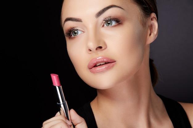 Conceito de beleza, cabeça e ombros de mulher olhando para cima e de lado, segurando batom rosa. retrato da beleza da modelo com lábios rosados pintado com brilho labial, estúdio com fundo preto, closeup
