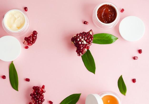 Conceito de beleza. cosméticos orgânicos naturais com extrato de romã, com ácidos de frutas, tampas vazias para texto, logotipo, em fundo rosa. lay plana, modelo, cópia espaço