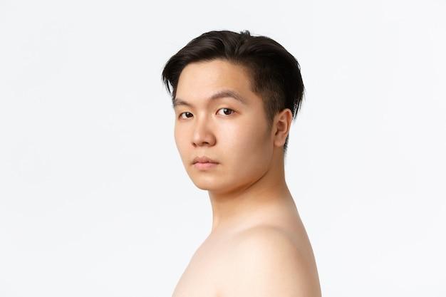 Conceito de beleza, cuidados com a pele e higiene. close de um homem asiático de aparência séria em pé, nu, sobre o branco