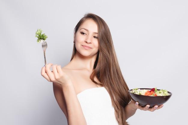 Conceito de beleza, cuidados com a pele e pessoas - linda menina morena na toalha, comendo salada fresca e sorrindo. mulher que come o alimento. linda mulher sorridente, tendo para jantar legumes frescos na cozinha.