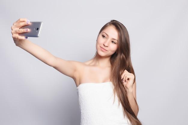 Conceito de beleza, cuidados com a pele e pessoas - mulher de spa. linda garota depois do banho, tocando seu rosto. pele perfeita. cuidados com a pele. hora da selfie. jovem mulher feliz tomando selfie. mimos. tratamento