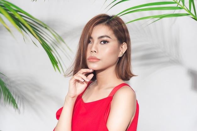 Conceito de beleza de verão. retrato de jovem mulher asiática com vestido vermelho Foto Premium