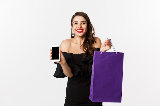 Conceito de beleza e compras. mulher bonita e elegante mostrando a tela e a bolsa do celular, comprando online, em pé sobre um fundo branco