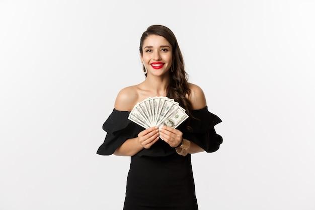 Conceito de beleza e compras. mulher elegante com lábios vermelhos, mostrando dólares e sorrindo, em pé sobre um fundo branco com dinheiro
