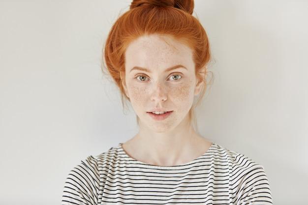 Conceito de beleza e cuidados com a pele. close-up foto isolada de uma ruiva jovem elegante e fofa com sardas e coque de cabelo com um sorriso encantador, em pé na parede branca, vestindo uma camisa de marinheiro