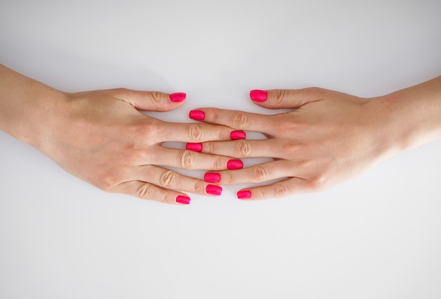 Conceito de beleza e cuidados com a pele. lindas mãos de uma jovem mulher e uma bela manicure em um fundo branco, flat-lay.