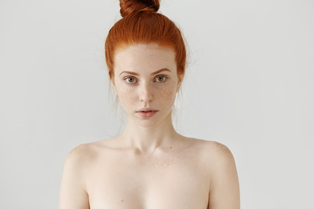 Conceito de beleza e cuidados com a pele. lindo europeu jovem gengibre feminino com características sensíveis olhando com sorriso sutil, posando de topless
