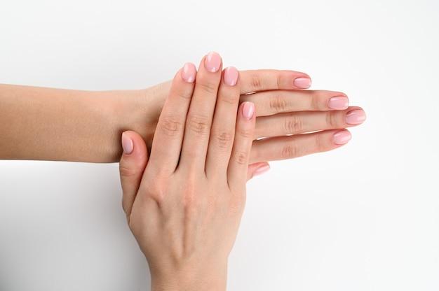 Conceito de beleza e cuidados com a pele - mão feminina com manicure pastel isolada no fundo branco.