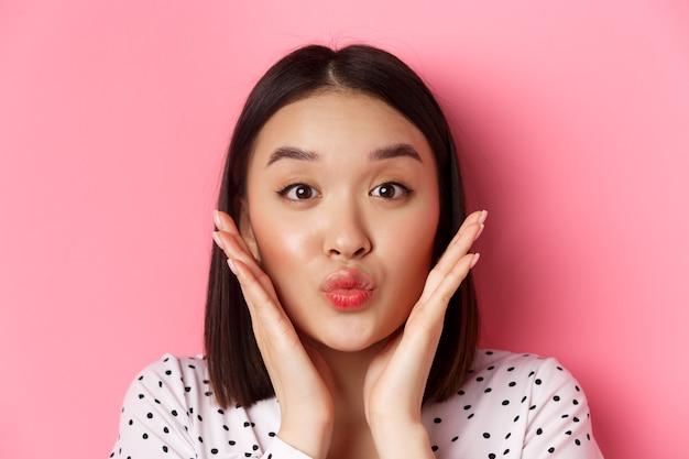 Conceito de beleza e estilo de vida. close-up de adorável mulher asiática tocando o rosto, lábios franzidos em um beijo, em pé rosa.