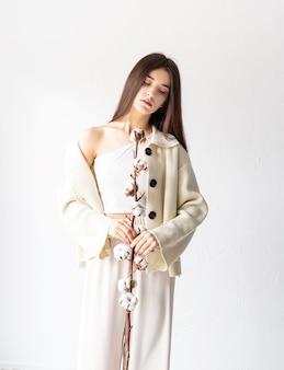 Conceito de beleza e juventude. mulher bonita com roupas aconchegantes segurando um ramo de flores de algodão
