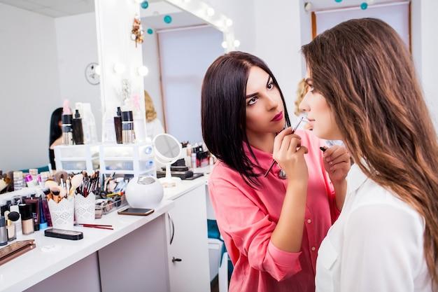 Conceito de beleza e maquiagem - closeup retrato de mulher bonita, ficando maquiagem profissional com pincel