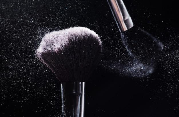 Conceito de beleza e maquiagem. escova de cosméticos, liberando uma nuvem de pó facial espumante rosa sobre fundo preto.