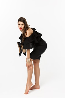 Conceito de beleza e moda. comprimento total da mulher sentindo dor nos pés