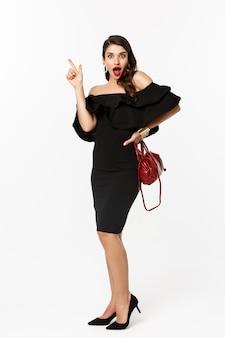 Conceito de beleza e moda. comprimento total de uma jovem animada num vestido glamour, lábios vermelhos, tendo uma ideia, levantando o dedo para sugerir algo, fundo branco.