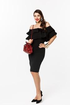 Conceito de beleza e moda. comprimento total de uma jovem elegante indo às compras de vestido preto, salto alto e bolsa, parecendo confiante, em pé sobre um fundo branco.