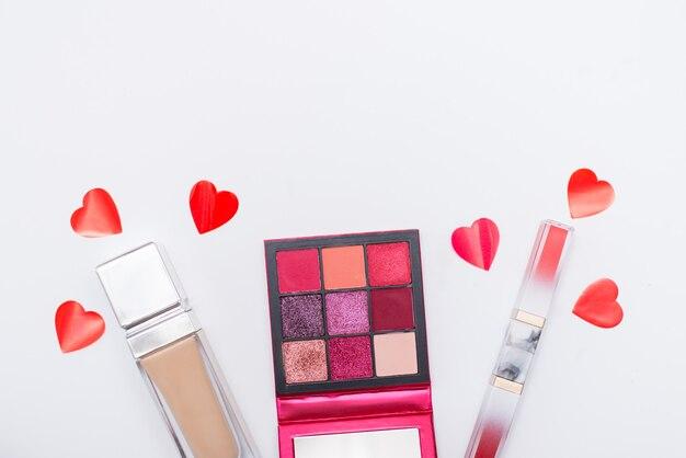 Conceito de beleza e moda. leigos planos de cosméticos e vermelhos corações isolados