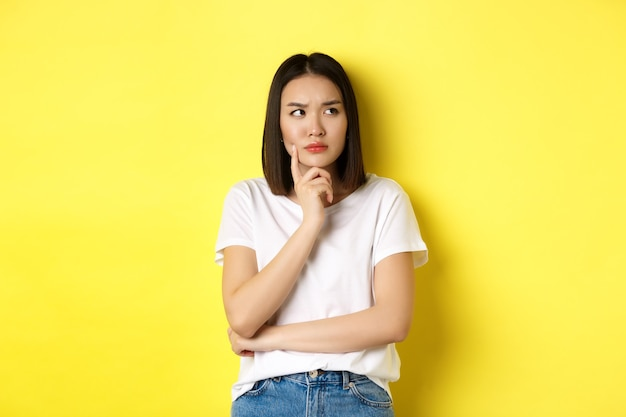 Conceito de beleza e moda. mulher asiática pensativa pensando, parecendo pensativa enquanto pondera algo, em pé sobre um fundo amarelo.