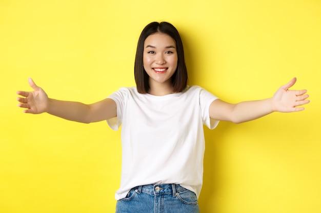 Conceito de beleza e moda. mulher asiática simpática espalhou as mãos e sorrindo, esperando por abraços, convidando-o, dar as boas-vindas a alguém e parecendo feliz, em pé sobre fundo amarelo.