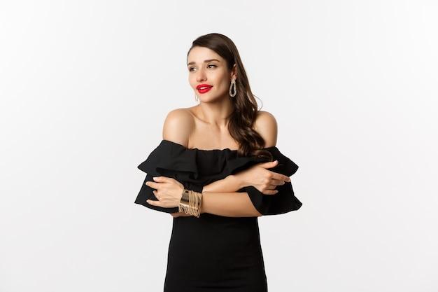 Conceito de beleza e moda. mulher elegante e bonita de vestido preto, maquiagem, abraçando-se e olhando para longe com olhar sensual, de pé sobre um fundo branco.