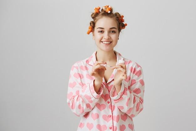 Conceito de beleza e moda. rapariga com rolos de cabelo e pijama a aplicar esmalte