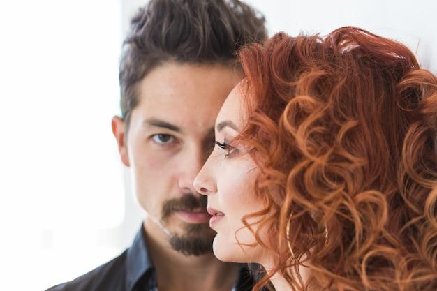 Conceito de beleza e pessoas - foto na cabeça de um casal com rostos sérios na parede branca Foto Premium