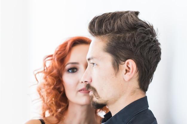Conceito de beleza e pessoas - foto na cabeça de um casal com rostos sérios na parede branca