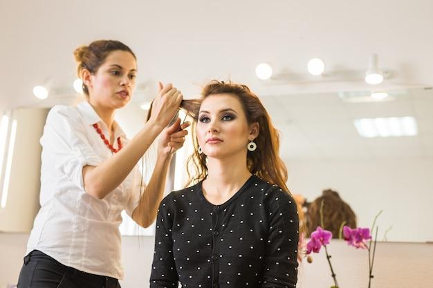 Conceito de beleza e pessoas jovem feliz com cabeleireiro em salão de cabeleireiro