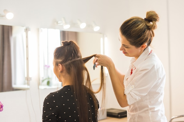 Conceito de beleza e pessoas - jovem feliz com cabeleireiro no cabeleireiro.