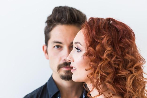 Conceito de beleza e pessoas - retrato de casal com rostos sérios sobre uma parede branca.