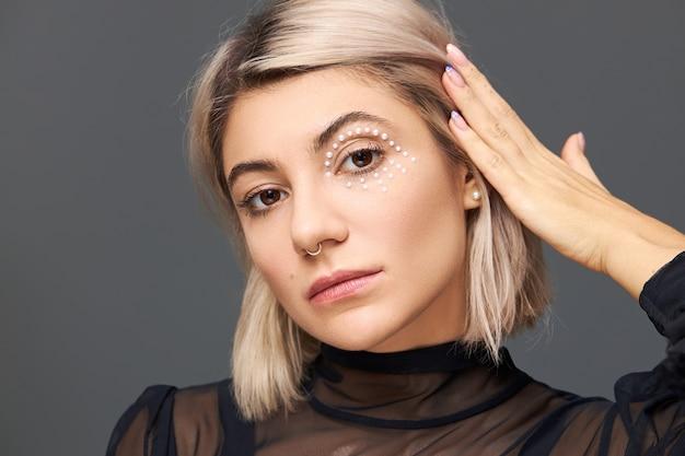 Conceito de beleza, estilo e feminilidade. linda e sensual mulher europeia com penteado loiro demonstrando sua maquiagem estilosa, cristais brancos ao redor dos olhos