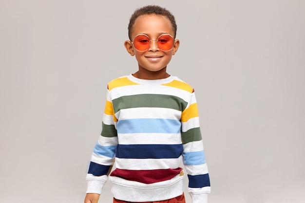 Conceito de beleza, estilo e moda. foto de um garoto africano elegante e alegre posando isolado, usando um suéter listrado elegante e óculos de sol redondos cor de rosa da moda, sorrindo feliz