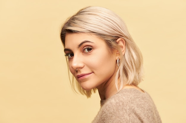 Conceito de beleza, estilo e moda. mulher atraente de 20 anos com piercing no nariz e cabelo bob tingido posando isolada com um sorriso enigmático e sedutor, vestida com um suéter de cashmere