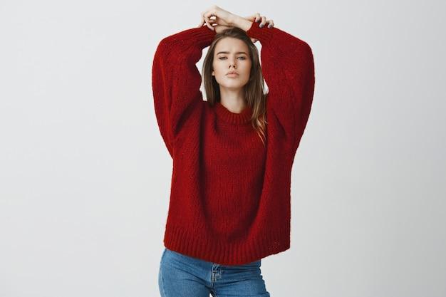 Conceito de beleza, estilo e sensualidade. mulher caucasiana atraente e segura de suéter vermelho solto, segurando as mãos na cabeça, apertando os olhos sexy e glamour com olhar quente posando contra