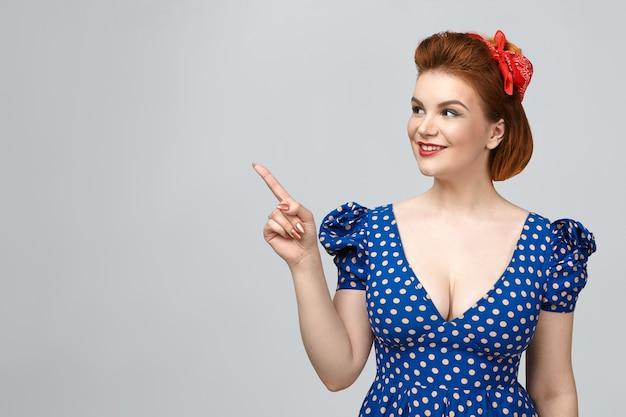 Conceito de beleza, estilo, moda e elegância. menina bonita vestida em estilo vintage pin up, mostrando espaço de cópia para sua informação, apontando o dedo indicador para a parede em branco do estúdio e sorrindo amplamente