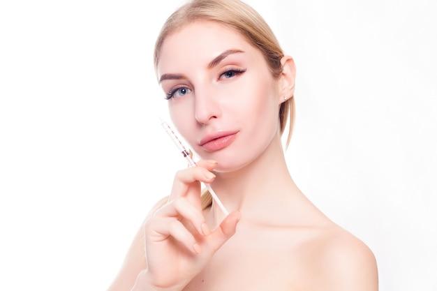Conceito de beleza, maquiagem e pessoas - mulher jovem e atraente recebe injeção plástica, isolada sobre fundo branco. mãos de médicos fazendo uma injeção no rosto. tratamento de beleza.