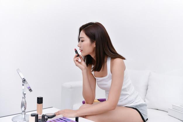 Conceito de beleza. menina bonita fazendo maquiagem em casa