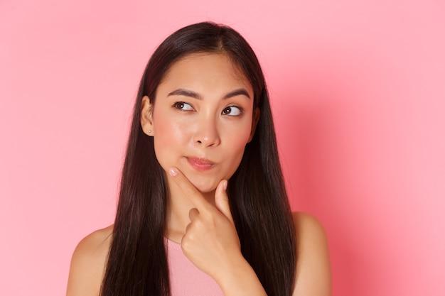 Conceito de beleza, moda e estilo de vida. close de uma menina asiática pensativa na moda, fazendo um plano, escolhendo algo, tocando o queixo e olhando o canto superior esquerdo enquanto pensa, parede rosa