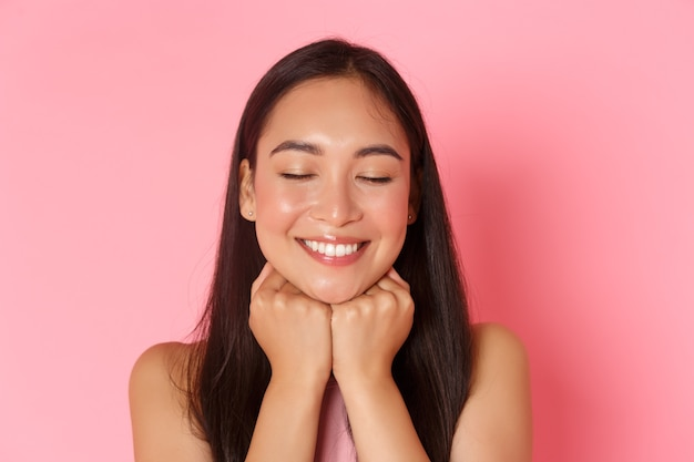 Conceito de beleza, moda e estilo de vida. close-up de uma garota asiática sonhadora e romântica, atraente, sonhando acordada, apoiando o rosto nas mãos e fechando os olhos com um sorriso branco feliz, parede rosa.