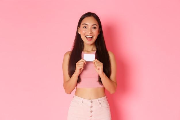 Conceito de beleza, moda e estilo de vida. menina asiática animada e divertida mal pode esperar para experimentar o novo cartão de crédito, mostrando desconto e sorrindo emocionada, em pé sobre a parede rosa indo às compras