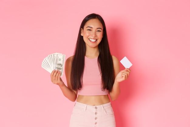 Conceito de beleza, moda e estilo de vida. menina asiática bonita alegre sorrindo e segurando o cartão de crédito com dinheiro, prefere usar o pagamento sem contato durante o coronavírus, parede rosa.