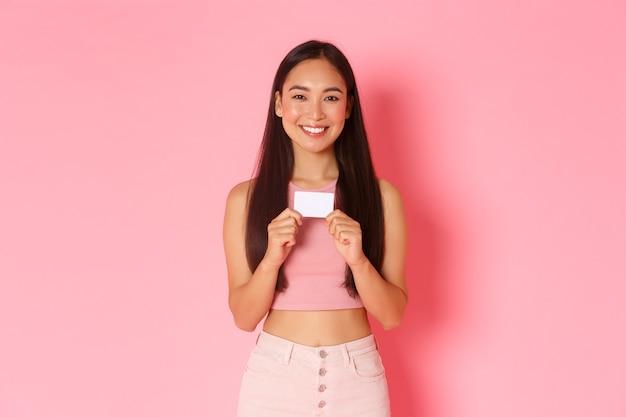 Conceito de beleza, moda e estilo de vida. retrato de uma linda garota asiática na moda mostrando seu cartão de crédito do banco e sorrindo. recomende a conta inicial ou confira o novo recurso de e-banking, parede rosa