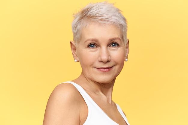 Conceito de beleza, moda, estilo, feminilidade e envelhecimento. retrato de mulher europeia de meia-idade, elegante e confiante, com uma pele bonita e elegante, olhos azuis e corte de cabelo de duende posando isolada, sorrindo