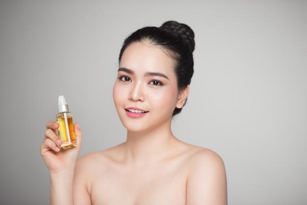 Conceito de beleza. mulher bonita asiática com pele perfeita segurando um frasco de óleo