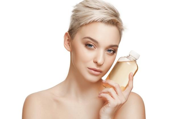 Conceito de beleza. mulher bonita caucasiana com pele perfeita segurando uma garrafa de óleo