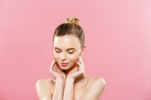 Conceito de beleza - mulher bonita com pele limpa e fresca, perto do estúdio rosa. cara de cuidados com a pele. cosmetologia.