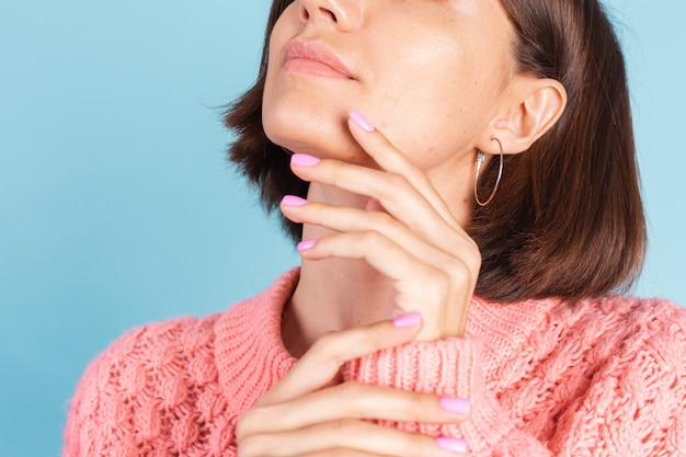 Conceito de beleza, mulher bonita com unhas rosa brilhante manicure na parede