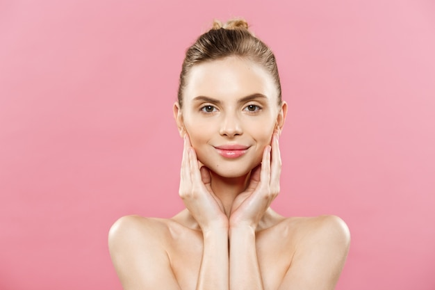 Conceito de beleza - mulher caucasiana bonita com pele limpa, maquiagem natural isolada no fundo rosa brilhante com espaço na cópia.