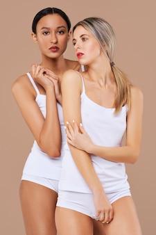 Conceito de beleza multiétnica. belas garotas caucasianas e africanas com pele saudável em calcinha branca e camisa
