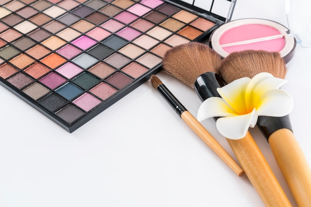 Conceito de beleza: paleta de sombras, blush compacto e pincéis de maquiagem